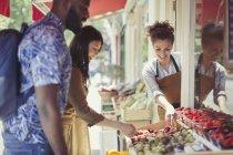 Працівник допомагаючи пара магазинів для фруктів на тротуарі магазину — стокове фото