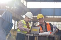 Male foreman and engineer working at laptop with blueprints in factory — Stock Photo