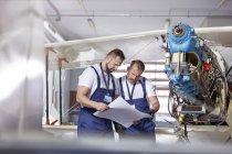 Male engineer mechanics examining plans, fixing airplane in hangar — Stock Photo