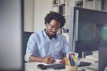 Бизнесмен заметок на компьютере в офисе — стоковое фото