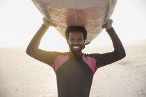 Портрет улыбающийся, уверенный в себе серфер, несущий доску для серфинга над головой на солнечном летнем пляже — стоковое фото