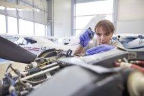 Concentré de mécanicien femme ingénieure avec lampe de poche examen moteur d'avion dans le hangar — Photo de stock