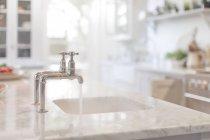 Вода з крана в кухонних раковині — стокове фото
