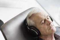 Senior man with headphones listening to music and reclining — Stock Photo