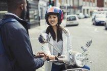 Lächelnde junge Frau auf Motorroller Gespräch mit Freund auf sonnigen urban street — Stockfoto