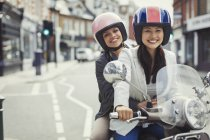 Smiling young women friends wearing helmets, riding motor scooter on urban street — Stock Photo