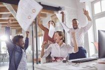 Gens d'affaires exubérante célébrant, jetant des formalités administratives frais généraux au bureau — Photo de stock