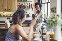 Улыбаясь Лесбийская Пара, наслаждаясь кофе и завтрак на кухне — стоковое фото