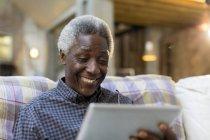 Homme senior souriant à l'aide de tablette numérique sur canapé — Photo de stock