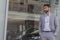 Portrait confident car salesman looking away outside car dealership showroom — Stock Photo
