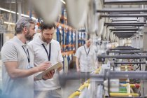 Male supervisor and worker with clipboard talking in fiber optics factory — Stock Photo