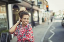 Portrait confident, laughing young woman on urban street — Stock Photo