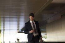 Empresário mensagens de texto com telefone inteligente no lobby do escritório — Fotografia de Stock