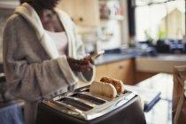 Женщина переписывается со смартфоном, поджаривает хлеб в тостере на кухне — стоковое фото