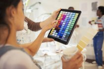 Young woman drinking coffee and viewing digital paint swatches on digital tablet — Stock Photo