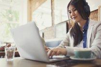Jeune femme à l'aide d'ordinateur portable et de boire du café au café — Photo de stock