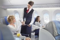 Flight attendant serving champagne to woman in first class on airplane — Stock Photo