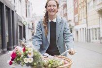 Mujer sonriente montando en bicicleta con flores en cesta - foto de stock