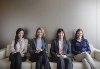 Portrait smiling businesswomen sitting in a row on sofa — Stock Photo