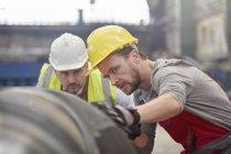Зосереджено чоловічого інженерів, вивчаючи стали частиною заводі — стокове фото