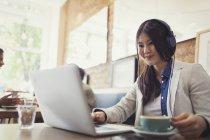 Усміхаючись молоду жінку, слухати музику з навушниками в ноутбук і п'ють кави в кафе — стокове фото