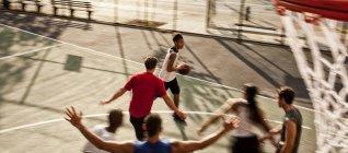 Мужчины играют в баскетбол на площадке — стоковое фото
