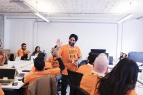 Hackers celebrating, high-fiving and coding for charity at hackathon — Stock Photo