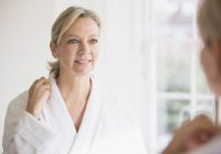 Smiling mature woman in bathrobe at bathroom mirror — Stock Photo
