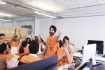Enthusiastic hackers cheering, coding for charity at hackathon — Stock Photo