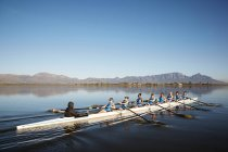 Female rowers rowing scull on sunny lake under blue sky — Stock Photo