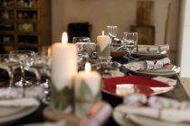 Candles, placesettings and Christmas crackers on table — Stock Photo