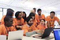 Hackers heureux à ordinateur portable codant pour la charité hackathon — Photo de stock
