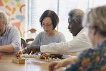 Senior friends playing mahjong at table in community center — Stock Photo