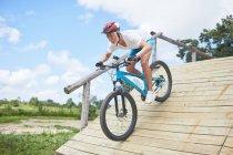 Цілеспрямований зрілою людиною на гірських велосипедах вниз смугу перешкод рампи — стокове фото