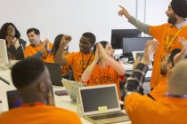 Happy hackers cheering and celebrating, coding for charity at hackathon — Stock Photo