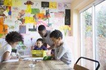 Afrikanischen Vater und Kinder Färbung am Tisch — Stockfoto