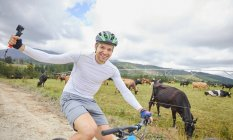 Portrait carefree man with wearable camera mountain biking on dirt road along cow pasture — Stock Photo