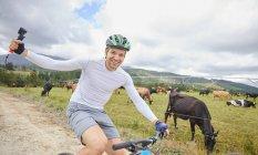 Портрет беззаботный человек с носимых камеры на горных велосипедах по грунтовой дороге вдоль корова пастбище — стоковое фото