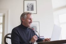 Smiling mature male freelancer working at laptop at home — Stock Photo