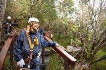 Улыбающаяся женщина готовится застегнуть канат в лесу — стоковое фото