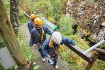 Друзі ходіння по мосту, підготовка до zip лінія — стокове фото