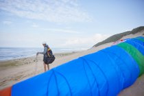 Male paraglider with parachute on ocean beach — Stock Photo