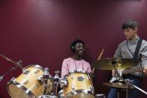 Adolescente musicisti registrazione di musica, suonare la batteria e chitarra in cabina suono — Foto stock
