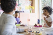 Toddler brother and sister eating breakfast at dining table — Stock Photo