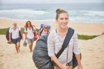 Retrato, Sonriente, seguro parapente femenino llevar mochila paracaídas en la playa - foto de stock