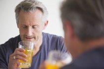 Mature man drinking juice at mirror at modern home — Stock Photo