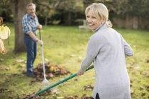 Mature caucasian couple with rakes working at garden — Stock Photo
