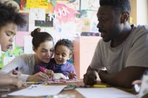 Happy multiracial family coloring at table — Stock Photo