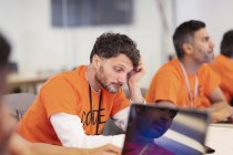 Focused hacker coding for charity at hackathon — Stock Photo