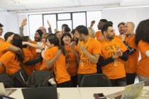 Happy hackers celebrating, coding for charity at hackathon — Stock Photo
